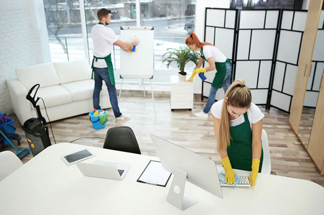 three people in aprons cleaning an office
