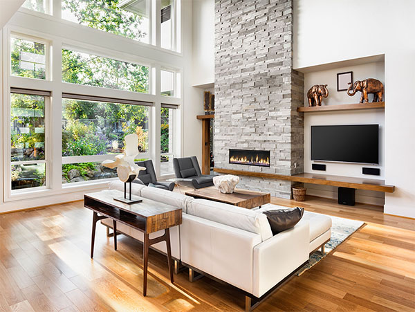 interior of a home living room with wood floors and a brick fireplace